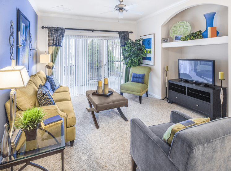 Staged furnished living room with carpet flooring, couch, chairs, coffee table, side tables with desk lamps, flat screen television, multi speed ceiling fan, and private patio access