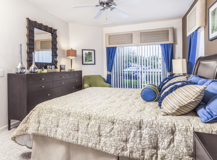 Furnished bedroom with carpet flooring, dresser, multi speed ceiling fan, night stands, and corner chair