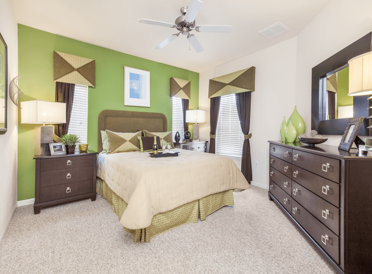 Staged furnished bedroom with carpet flooring, night stands, desk lamps, dresser, wall mounted mirror, and multi speed ceiling fan