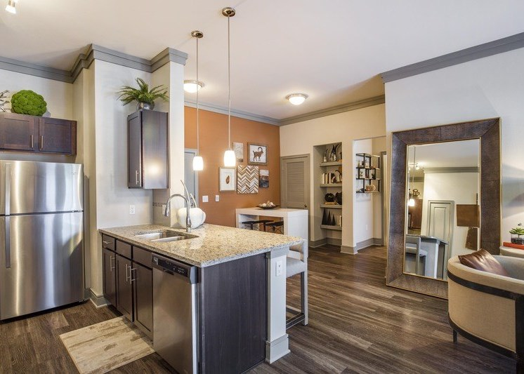 Kitchen and dining room with hardwood style floors and an orange accent wall