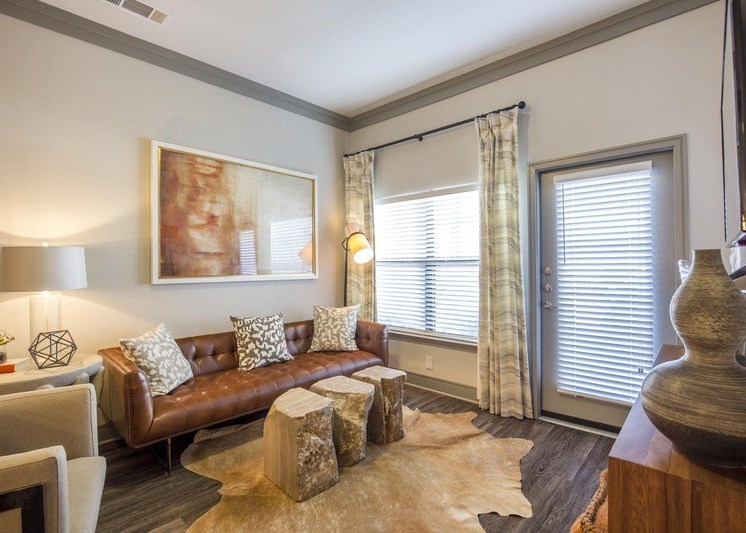 Living room with brown rug, white walls, gray trim, and a brown leather sofa