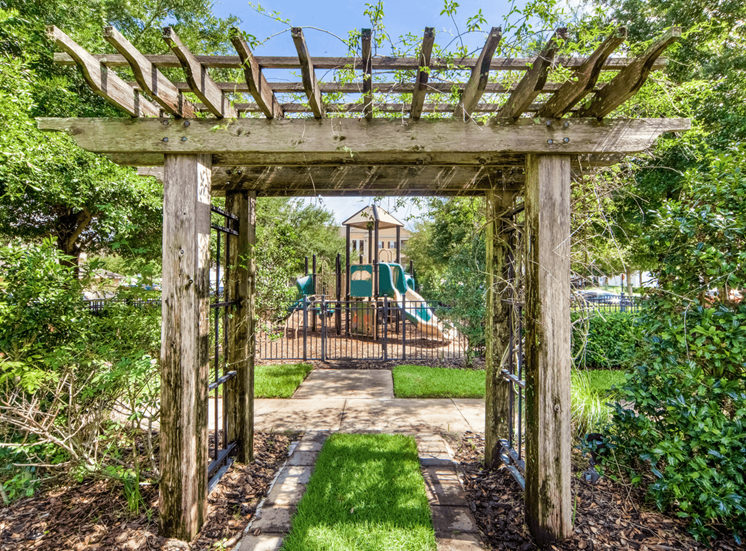 Outdoor playground with slides and monkey bars surrounded by native landscaping