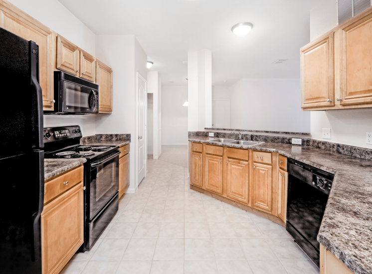 Fully equipped kitchen with black appliances and kitchen breakfast bar
