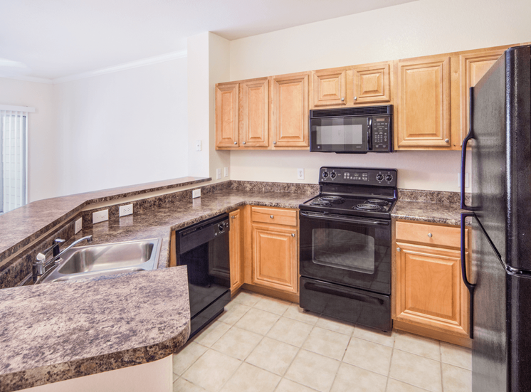Fully equipped kitchen with black appliances and tiled flooring