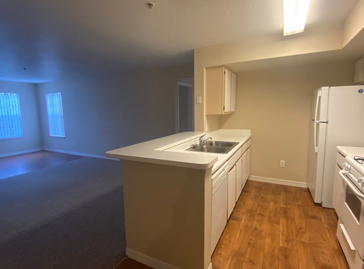 Kitchen featuring white cabinets, white appliances, white countertop, gas stove, view of living room, view of two widows in living room