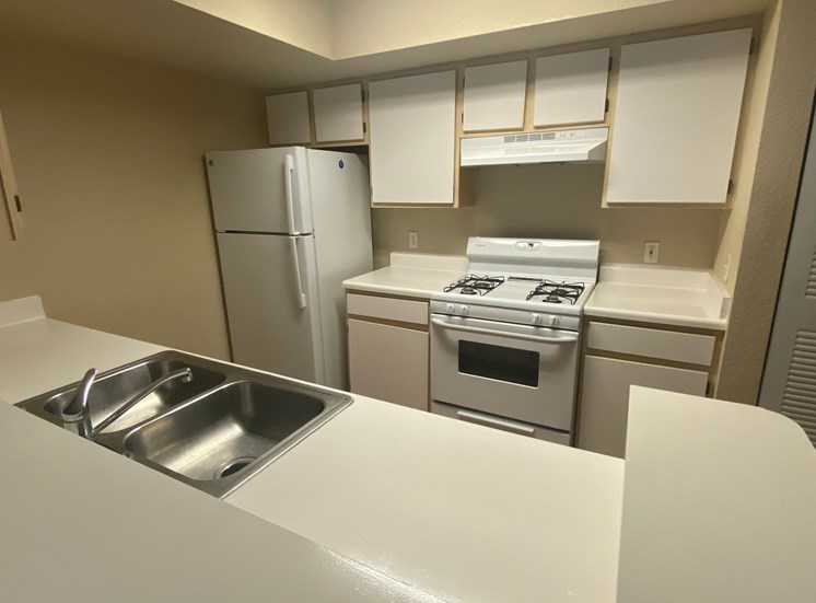 Kitchen featuring white cabinets, white appliances, white countertop, gas stove, folding door pantry