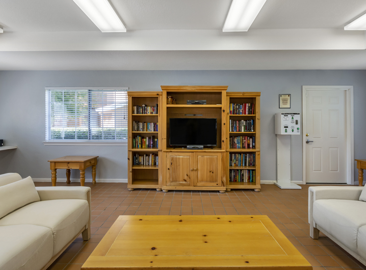 Clubhouse lounge with couches, coffee table, book shelving, and television
