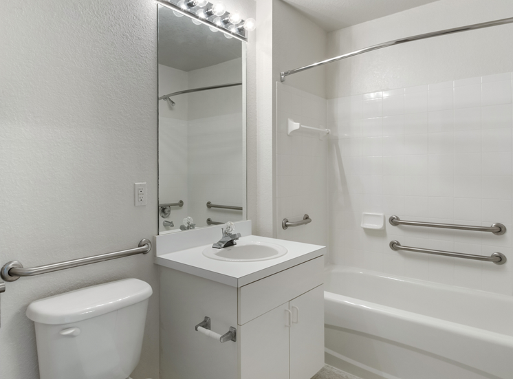 Bathroom with vanity lighting, large mirror, and tiled shower