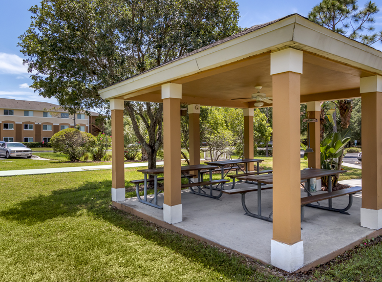 Outdoor covered picnic area surrounded by native landscaping
