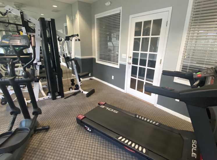 Carpeted fitness center with treadmill, elliptical, weight machines, and dual tone paint