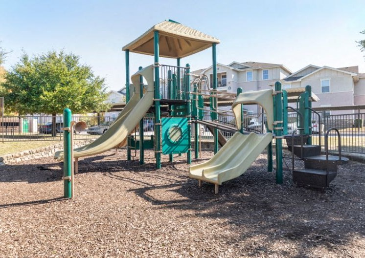 Outdoor playground with a yellow and green color scheme and apartment building in the background