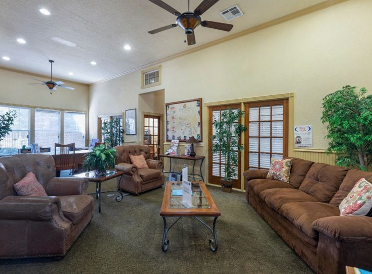 Clubhouse interior with brown sofa and leather recliner, a ceiling fan, and large green plants