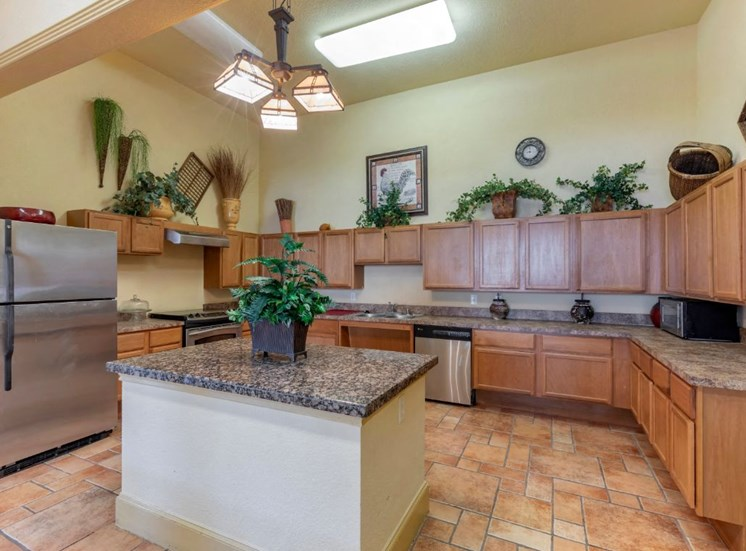 Clubhouse interior kitchen area with wooden cabinetry and kitchen island
