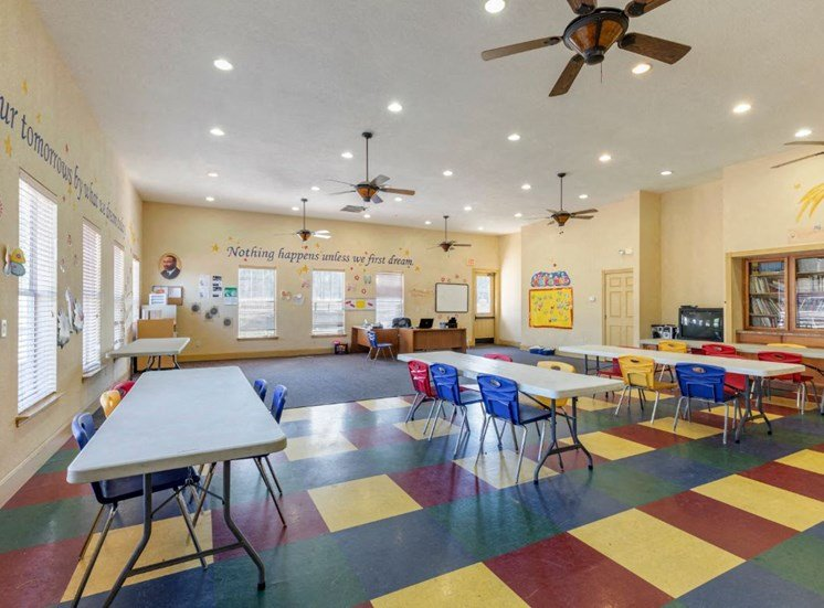 Activity center with white rectangle tables, blue, red, and yellow chairs, and a red and yellow patterned floor