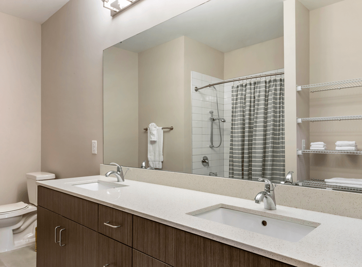 Model Bathroom with Brown Cabinets White Counter Wire Shelving Next to Bathtub