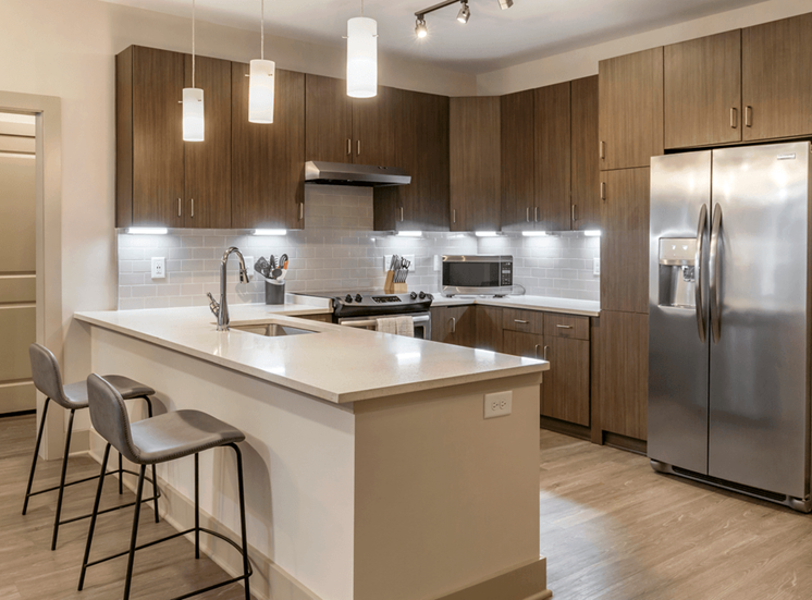 Model Apartment Kitchen with Brown Cabinets, Stainless Steel Appliances, White Counters, and Breakfast Bar with Bar Chairs