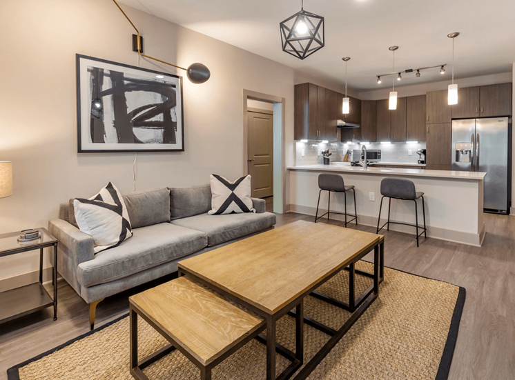 Model Living Room with Contemporary Furniture and Art Next to Kitchen with Breakfast Bar
