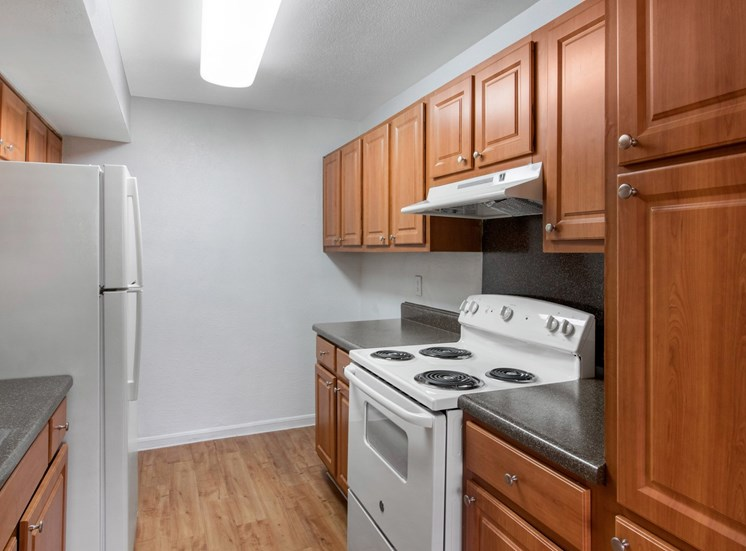 Fully equipped kitchen with hardwood style flooring and white appliances