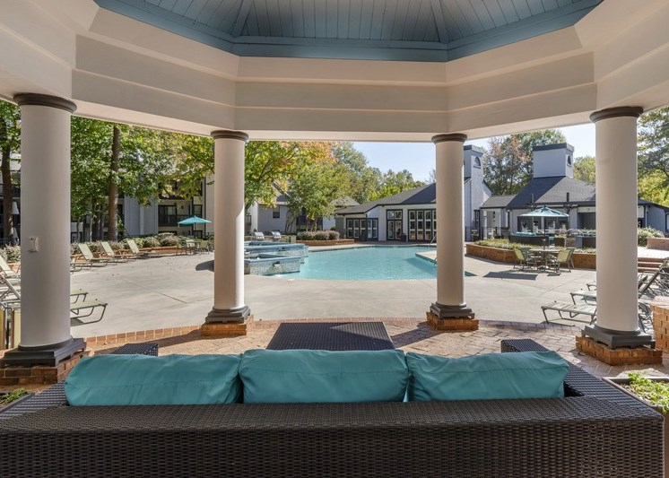 resident lounge under a gazebo with white columns, area overlooking swimming pool, turquoise and brown couch with brown whicker ottoman, lime green chaise lounges