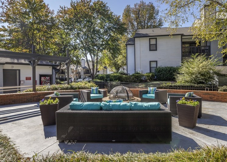 outdoor resident lounge area with fire-pit, brown whicker couch with turquoise cushions, four brown whicker chairs with matching turquoise cushions, area surrounded by white and gray apartment buildings