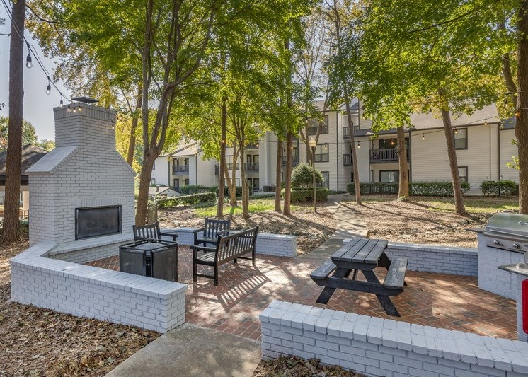 Bricked community grilling area with gas grills, picnic table, bench and chairs, trash can, and outdoor fireplace with surrounding low brick wall with mature trees and building exteriors in the background.