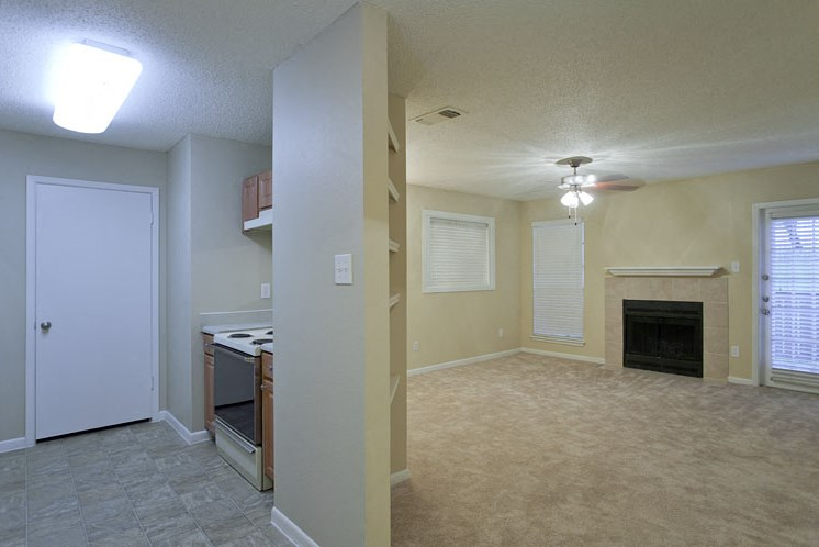 Open Layout Floor Plan View of Kitchen and Carpeted Living Room with Fireplace and Built in Shelf