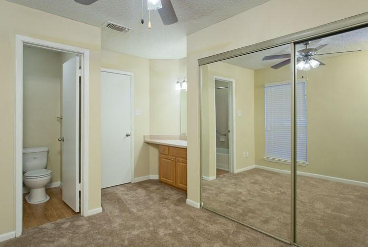 Open Layout Bedroom with Mirror Sliding Closet Doors Next to Vanity