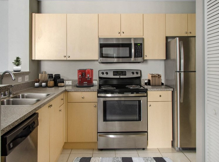 Fully Equipped Kitchen with Stainless Steel Appliances, Grey Counters, Blonde Wood Cabinets and Decorations