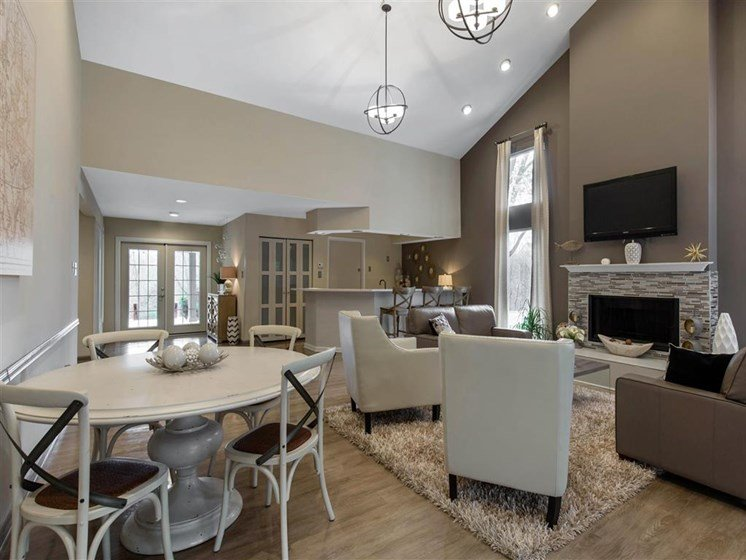 Clubhouse with White Dining Table and Chairs Next to Seating Area with White Chairs on Area Rug  with Grey Loveseats Around Fireplace with Mounted TV Above it