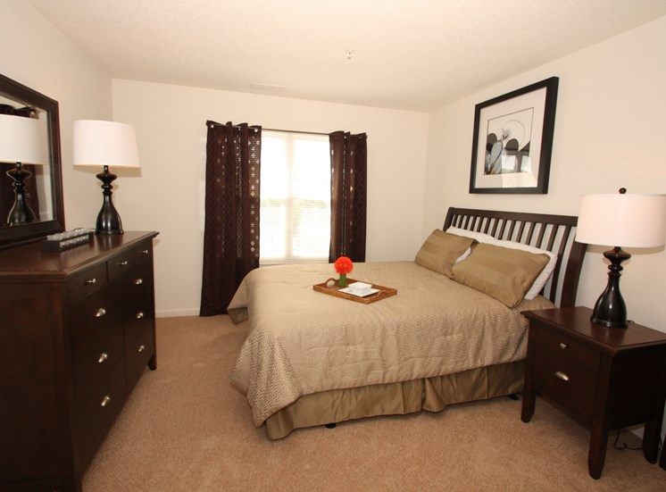 Bedroom with a queen size bed, dresser and lamp with a Large window