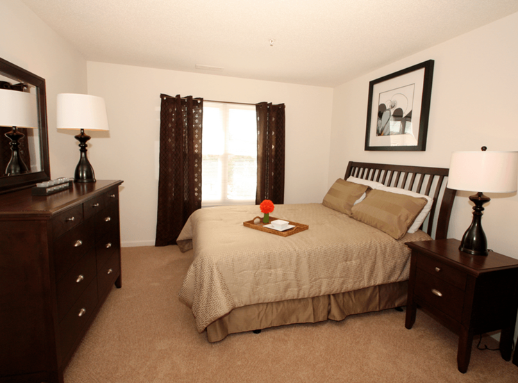 Bedroom with carpet flooring, dresser, bed, night stand, wall art, and large window with curtains