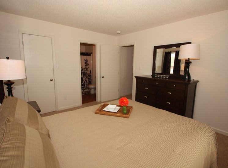 Bedroom with queen size bed, night stand with lamp . Dresser with a lamp  and mirror.