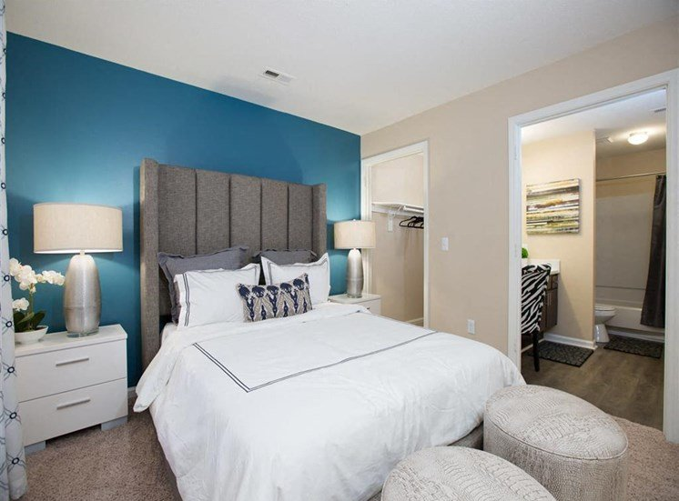 Model Bedroom with Blue Accent Wall Bed with Grey Headboard Nightstands and Dresser and En Suite Bathroom and Walk in Closet