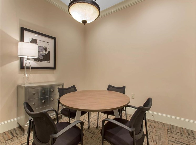 Clubhouse Seating Area with Round Dining Table with Chairs and Chest of Drawers with Art on the Wall
