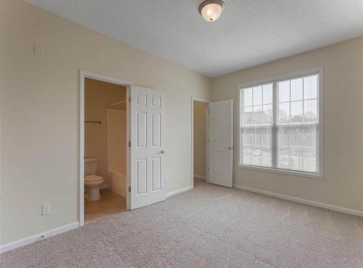 Carpeted Bedroom with Large Window En-Suite Bathroom and Walk-in Closet