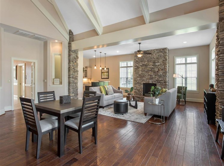 Clubhouse Seating Area with Dining Room Table with Chairs  Grey Couches Triangle Glass Coffee Table Brick Fireplace with Windows and Decorations