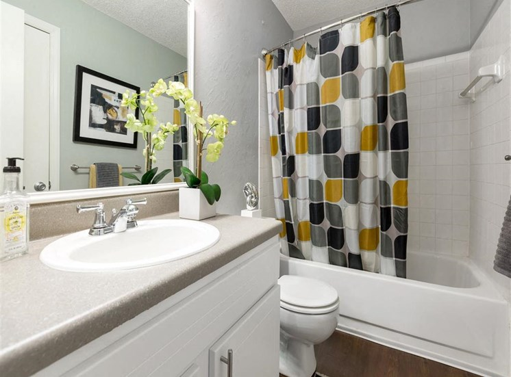 Model Bathroom with Grey Counters White Cabinets and Earth Tone Shower Curtain