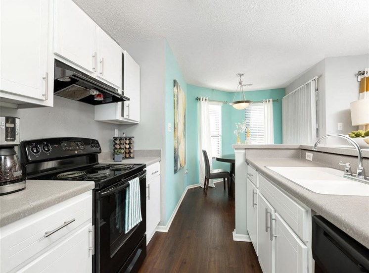 Decorated Kitchen with White Cabinets Grey Counters Double Sink and Black Appliances and Blue Dining Room with Windows and Chair with Tables