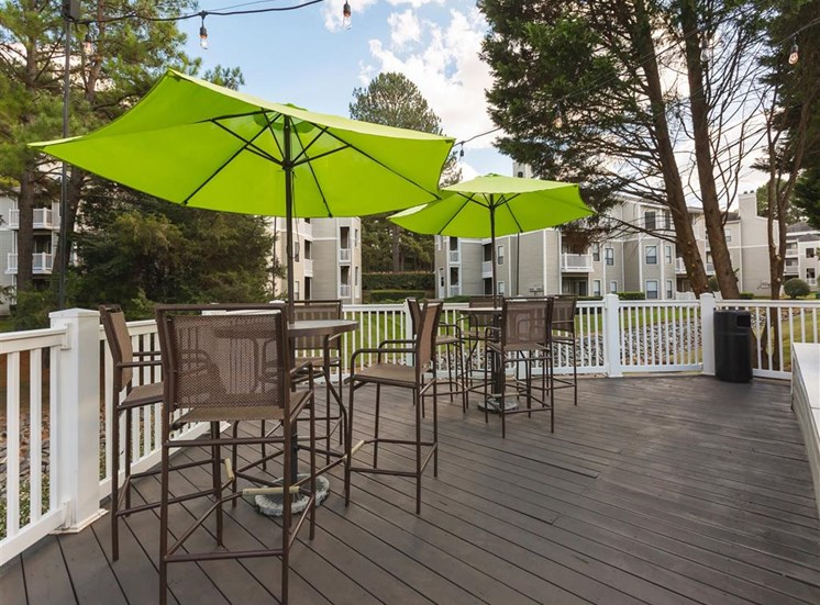 Deck Patio with Bar Height Picnic Tables with Bright Green Umbrellas Net to White Railing with Trees and Building Exteriors in the Background