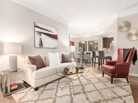 Spacious Carpeted Living Rooms with White Couch Red Armchair Glass Coffee Table  on White Area Rug with Dining Room in the Background