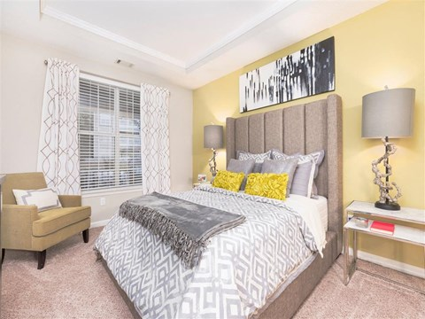 Model Bedroom with Large Grey Cushion Headboard with Armchair in the Corner and Night Stands