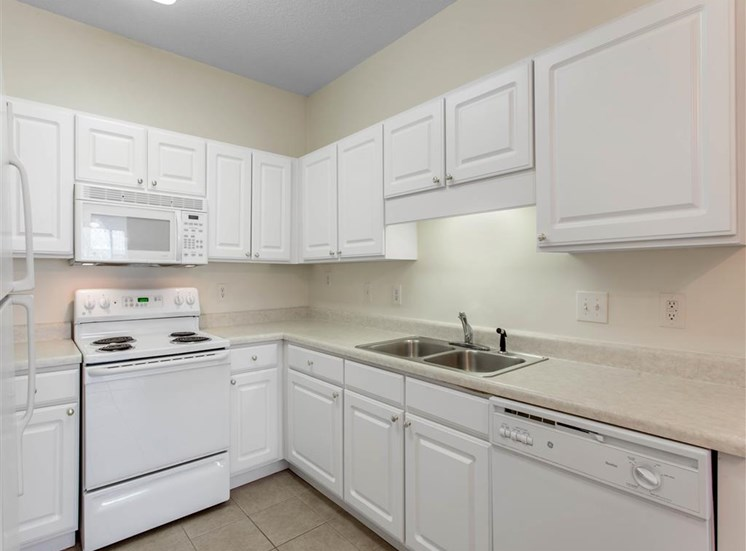 Kitchen with White Cabinets and Appliances with White Counters