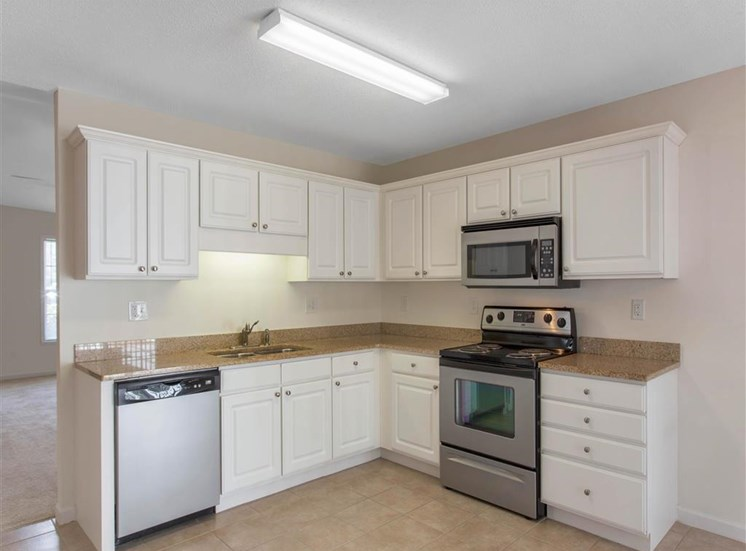 Kitchen with White Cabinets and Stainless Steel Appliances with Brown Counters