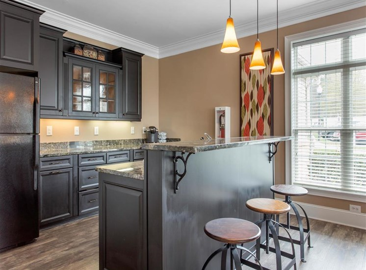 Clubhouse Breakfast Bar with Barstools Grey Counters and Black Cabinets Next to Large WIndow