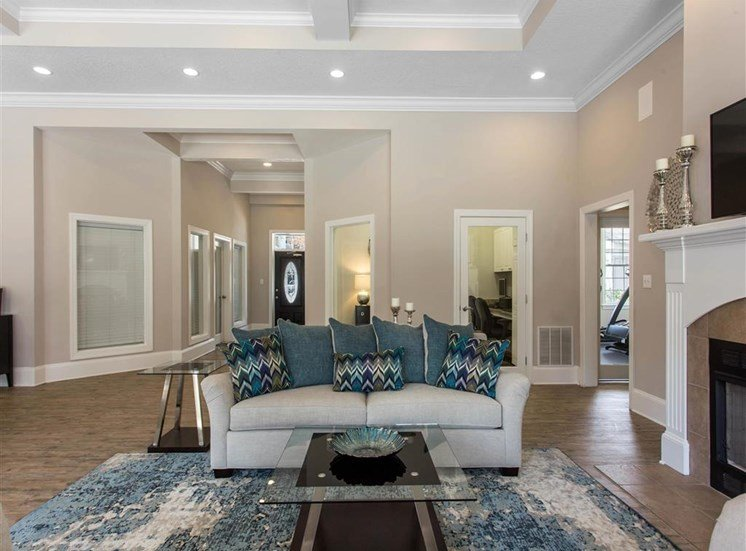 Clubhouse Seating Area with White Couch on Blue Area Rug with Glass Coffee Table Next to Fireplace