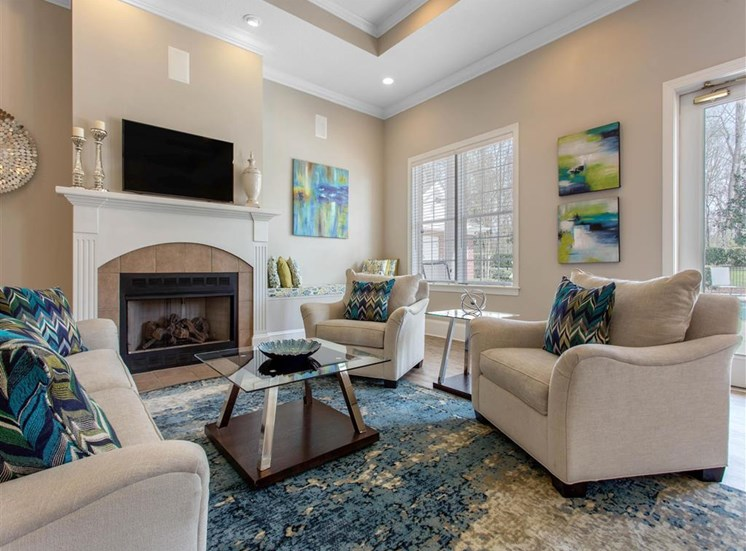 Clubhouse Seating Area with White Couch and Armchairs on Blue Area Rug with Glass Coffee Table Next to Fireplace