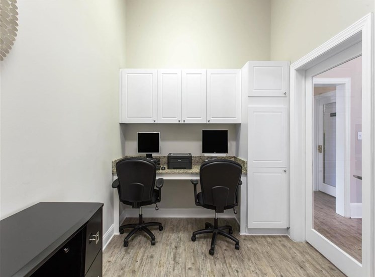 Business Center with Computers and a Printer on Grey Counter with Rolling Chairs Below White Cabinets