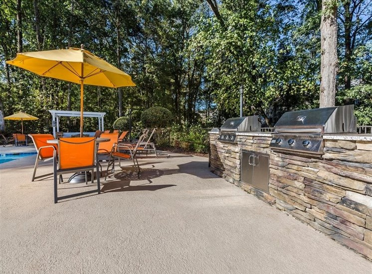 Summer Kitchen Grilling Area Next to  Picnic Tables with Orange Chairs and Yellow Umbrellas Near Fence with Trees in the Background