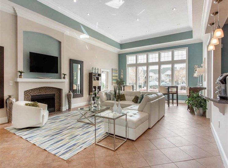 Clubhouse Seating Area with White Couch Glass Coffee Table and End Tables on Area Rug in Front of Bright Window