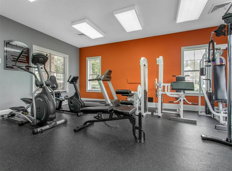 Fitness Center with Exercise Equipment and Orange Accent Wall